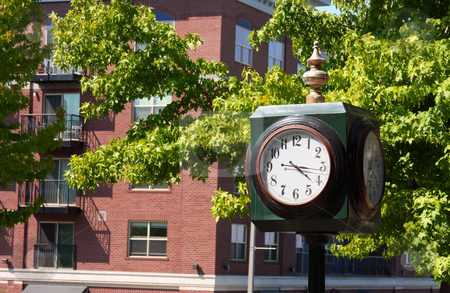 Street Corner Clock stock photo, Street corner clock with trees and buildings in the background. by Steve Stedman