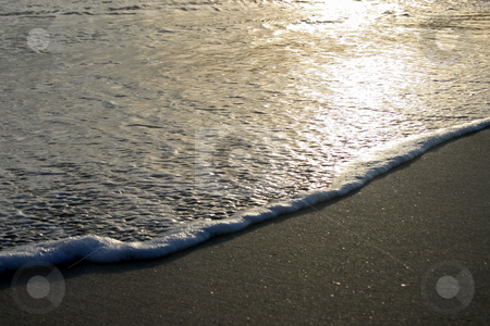 Waves stock photo, Waves coming ashore, at sunset, beach and foam. by Lucy Clark