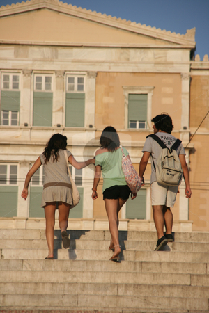 Teens walking in athens stock photo, Three young teens walking in athens with greek parliament blur in background by EVANGELOS THOMAIDIS