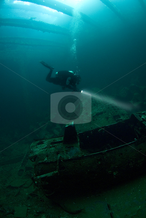 Diver with Zero Airplane stock photo, A diver inspects the fuselage of a Japanese Zero fighter plane, found in the hold of the Fujikawa Maru, an aircraft transport sunk during Operation Hailstone, Febuary 1944, in Truk (Chuuk) Lagoon, Micronesia during World War II by A Cotton Photo