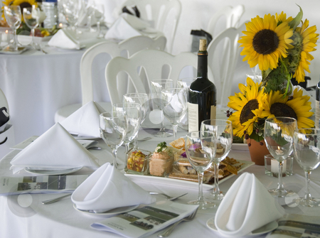 Luncheon Table stock photo, Stock photo of an elegant table set for a luncheon in the country.  There is a vase of sunflowers for a centerpiece, a bottle of wine and an assortment of dips and crackers on the table.  Programs for the day's events are at each place setting. by Maria Bell
