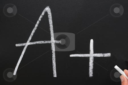 A teacher writing A+ on a blackboard. stock photo, A teacher writing A+ on a blackboard. by Stephen Rees