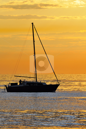 Sailboat at sunset stock photo, Silhouette of a boat navigating on the sea at the sunset by Massimiliano Leban