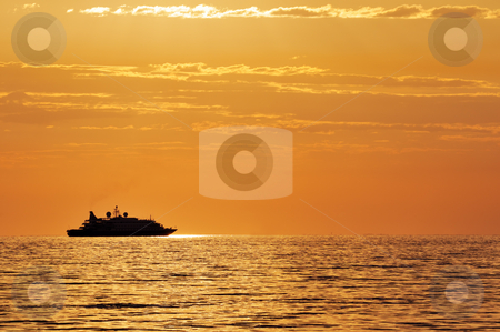 Passenger ship at sunset stock photo, Boat silhouette on a quiet sea at twilight by Massimiliano Leban