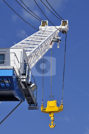 Crane stock photo, Blue and white crane with a yellow hook against a blue sky by Massimiliano Leban