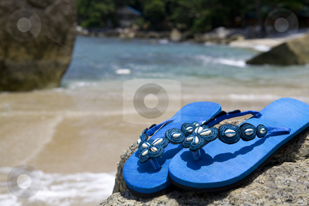 Sandals on a rock at the beach stock photo, Blue beach sandals on a rock at the beach by Magdalena Ascough