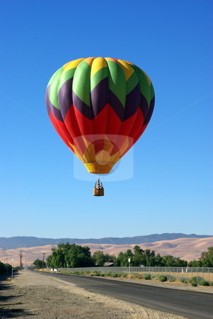 Landing A Hot Air Balloon stock photo, A multi colored Hot Ait Balloon coming in for a landing. by Lynn Bendickson