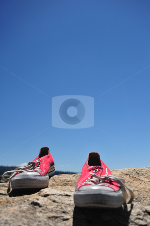 Red Tennis Shoes Alone stock photo, A pair of red tennis shoes by them selves on granite with a bright blue sky in the background. by Lynn Bendickson
