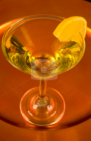 Yellow cocktail on a bronze tray stock photo, Closeup of a yellow cocktail with a slice of orange on a bronze tray by Magdalena Ascough