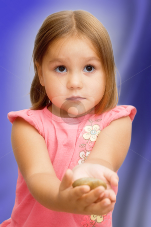 Innocent Gift stock photo, A young girl holding out a rock as a gift by Richard Nelson