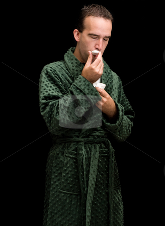 Flu Virus stock photo, A young man taking his temperature and wearing a bathrobe by Richard Nelson