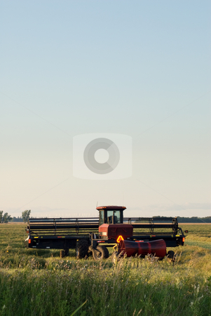 Farm Machinery stock photo, A combine in a field with copyspace available in the sky by Richard Nelson