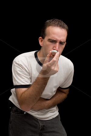 Stomach Ache stock photo, A young man taking his temperature and holding his stomach by Richard Nelson