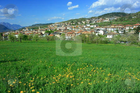 Alpine town stock photo, Beautiful alpine town with green field by Natalia Macheda