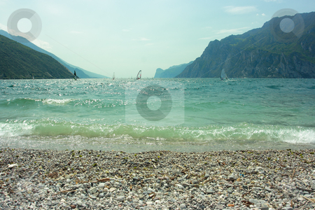Surfers on Garda lake stock photo, Beautiful view on Garda lake with people practicing surf-riding by Natalia Macheda