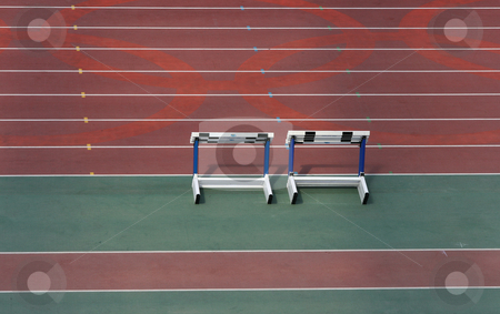Race track stock photo, Detail from empty athletics race track and stack of hurdles by EVANGELOS THOMAIDIS