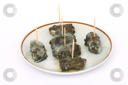 Leafs wraps on dish stock photo, Cooked wraped and stuffed grape leafs with rice and meat traditional greek food dolmadakia with tooth sticks on dish by EVANGELOS THOMAIDIS