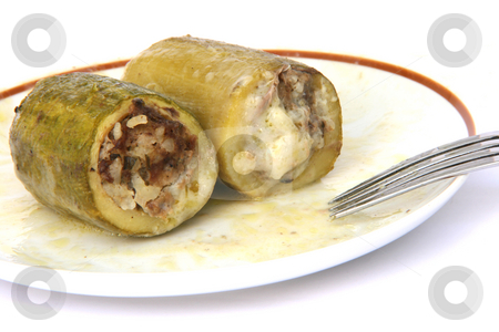 Stuffed courgettes on dish stock photo, Two Baked stuffed courgettes on dish with fork isolated on white traditional greek cuisine by EVANGELOS THOMAIDIS