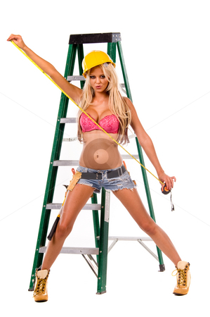 Sexy Construction Worker stock photo, High fashion glamour model in daisy duke shorts, tool belt, pink bra and yellow hard hat on a ladder with a measuring tape by Robert Deal