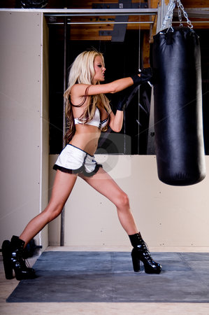 Sexy MMA Fighter stock photo, Sexy blond female MMA fighter training in the gym punching the heavybag by Robert Deal