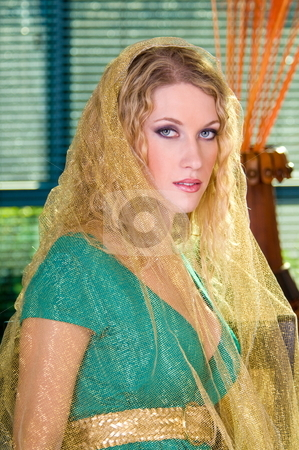 Beautiful blond woman. stock photo, Blond woman wearing a green dress with gold shimmery fabric covering her head. by Robert Deal