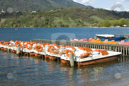 Catamarans on Caldonazzo lake stock photo, Row of colorful catamarans with buoys near wooden quay on Italian Caldonazzo lake near Trento by Natalia Macheda