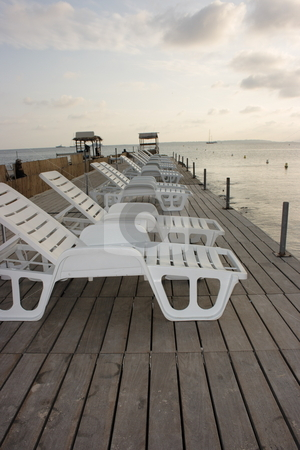 Chaise longues on pier stock photo, Row of white chaise longues on a wooden pier in sunset light by Natalia Macheda