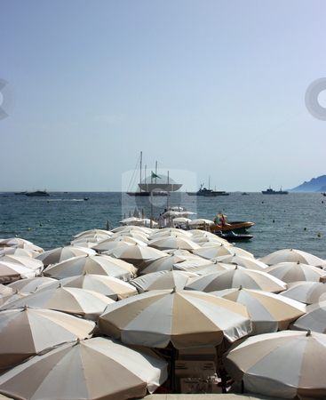 Dense beach umbrellas stock photo, Beach umbrellas on a pier with restaurant tables. Kannes, France by Natalia Macheda