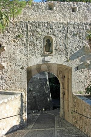 Exit out of castle stock photo, A fragment of city-castle Saint Paul-de-Vence: pavemented roads goes under arc exit with a statue of Saint Paul over it. by Natalia Macheda