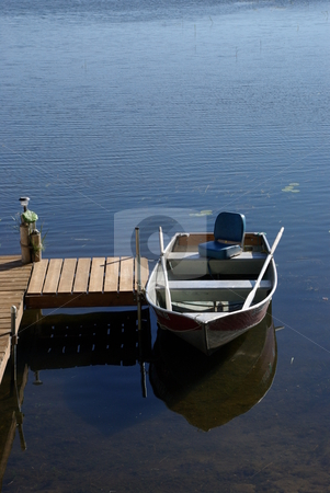 Rowboat at  Dock stock photo, Morning summer sun brightens a 12' rowboat tied to a dock on a northcentral Minnesota Lake. The little fishing boat appears to be waiting for its owner on a calm, bright day. by Dennis Thomsen
