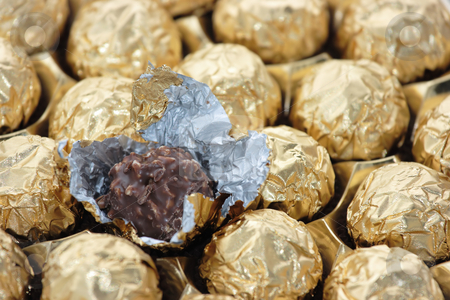 Golden sweets stock photo, Set of chocolate sweets in golden foil, one sweet is free of foil by Natalia Macheda