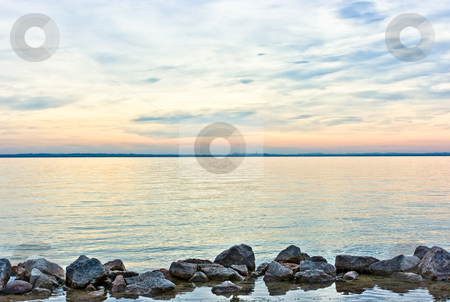 Horizontal theme stock photo, Horizontal theme by means of stones, water, skyline, and sky during dramatic sunset over lake Garda, Italy by Natalia Macheda