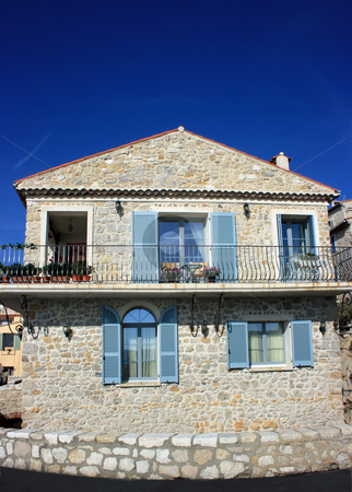 French house stock photo, House with stone facing, blue shutters and elegant balcony near road in Antibes, French riviera. There is also an old-fashioned carriage for babies on the balcony at the right. by Natalia Macheda
