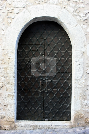 Medieval massive door stock photo, Massive wooden door with cast-iron decoration in a stone wall of medieval castle-city Saint Paul-de-Vence. Southern France by Natalia Macheda