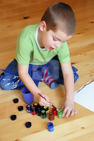 Boy painting on floor stock photo, A boy is painting on the floor by Ivan Paunovic