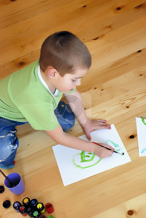 Boy painting with brush stock photo, A boy is painting on the floor by Ivan Paunovic