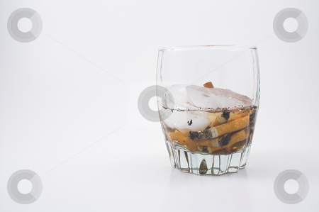 Cigarettes in a Glass stock photo, Cigarette butts in a glass of ice. by Robert Byron