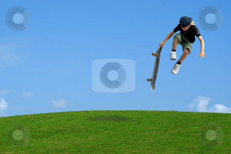 Skater stock photo, Young skater jumping over the green hill with skateboard in hand by Serge VILLA