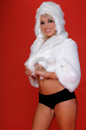 Happy Snow Bunny stock photo, Sexy blond snow bunny in a white furry coat and hat and black hot pants over a red background by Robert Deal