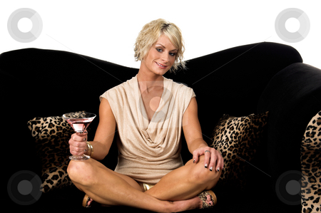 Party Doll stock photo, Pretty young blond woman in a tan dress sitting cross legged on a black velvet couch with a martini at a party by Robert Deal
