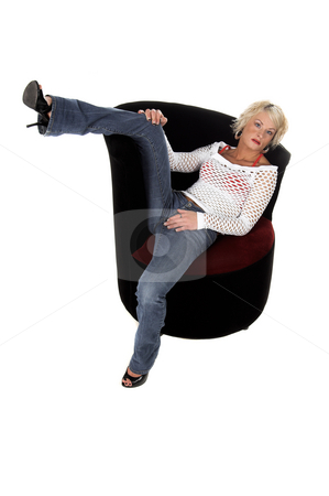 Blond In Velvet Chair stock photo, Fullbody shot of a pretty blonde with short hair in a mesh top and jeans sitting in a velvet wing backed chair by Robert Deal