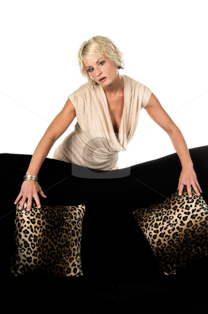 Pretty Blonde Behind Couch stock photo, Pretty blonde with short hair and a nice smile wearing a metallic tan cowel neck dress standing behind a couch straighting pillows by Robert Deal