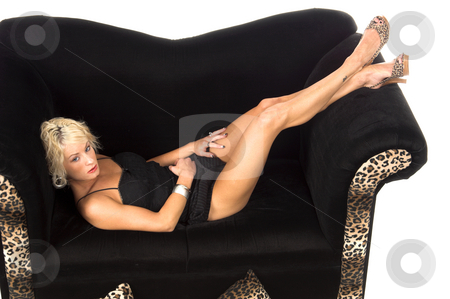 Pretty Blond Laying On Couch stock photo, Pretty blonde with short hair in a short balck dress laying on a black and lepoard print couch with her feet in the air by Robert Deal