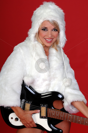 Winter Rock N Roll   stock photo, Sexy blond snow bunny in a white furry coat and hat and black hot pants over a red background with an electric guitar by Robert Deal