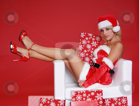 Santa's Helper stock photo, Sexy Mrs Santa Clause sitting with her legs over the arm of a snow white chair surrounded by Christmas gifts by Robert Deal