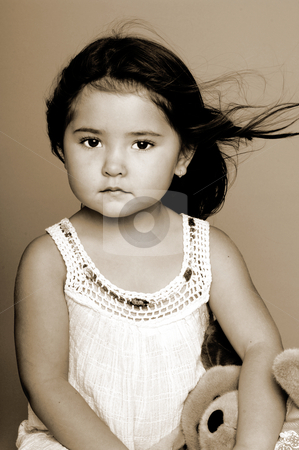 Little Girl Portrait Sepia stock photo, Little girl sitting on a grey background and holding a stuffed toy by Robert Deal