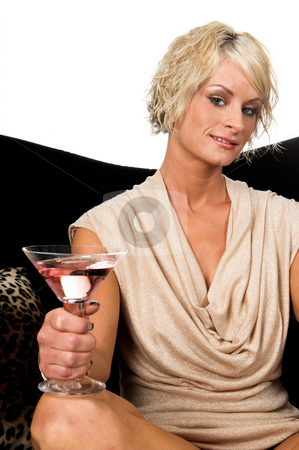 Party Doll stock photo, Pretty young blond woman in a tan dress relaxed on a black velvet couch with a martini at a party by Robert Deal