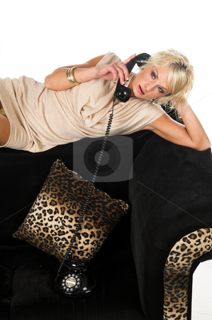 Blond Couch Retro Phone stock photo, Pretty blonde with short hair and a nice smile wearing a metallic tan cowel neck dress laying across the back of a black and lepoard couch talking on a retro phone by Robert Deal