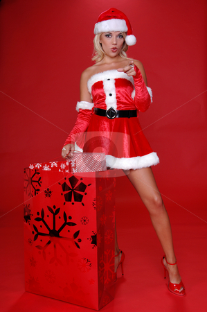 Santa Wants You stock photo, Sexy Mrs Santa with a large bag full of christmas gifts points her finger at the viewer and mouths the word