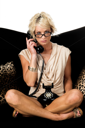 Cross legged on a  Retro Phone stock photo, Pretty blonde with short hair and a nice smile wearin glasses and a metallic tan cowel neck dress sitting cross legged on a black and lepoard couch talking on a retro phone by Robert Deal